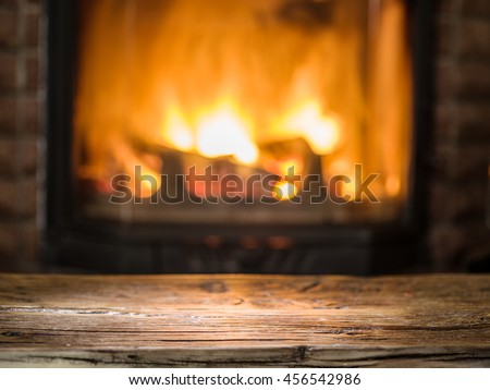 Old wooden table and fireplace with warm fire on the background. - stock photo