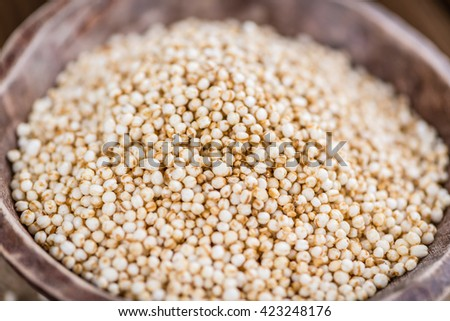 Old wooden table with a portion of puffed Quinoa as detailed close-up shot (selective focus)