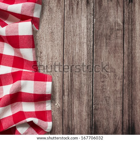old wooden table with red picnic tablecloth and copyspace - stock photo