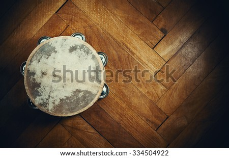 Old wooden tambourine on brown parquet.  - stock photo