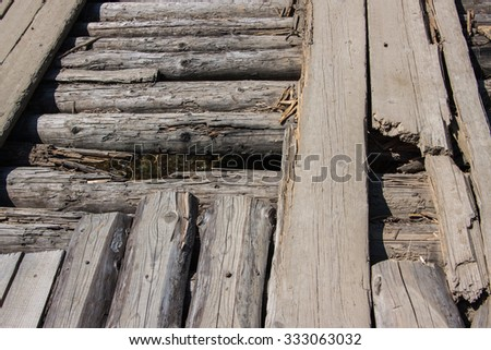 old wooden texture. rotten logs and boards. Destruction of the old wooden bridge - stock photo