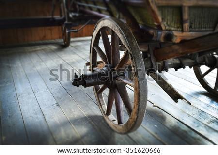 Old wooden wagon wheel - stock photo