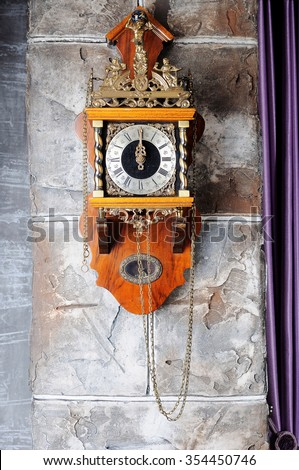 Old wooden wall clock on an impressive wall. Interior detail. - stock photo
