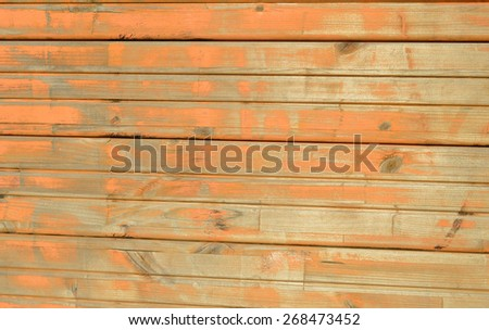 Old wooden wall with worn out paint. Grungy aged exterior wall of old building. Painted house wall. Weathered warehouse wall. Orange painted wall, dirty and old texture. - stock photo