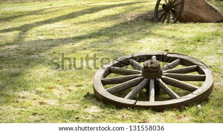 Old wooden wheel is on the ground