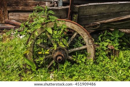 Old wooden wheel near log barn - stock photo