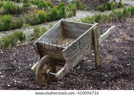 Old wooden wheelbarrow in garden.