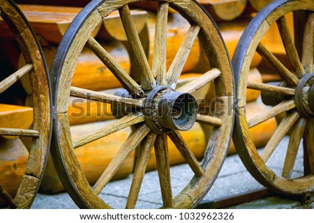 old wooden wheels on hose wall background
