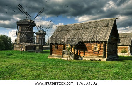 Old wooden windmill and wooden house from bars in Suzdal town, Russia. Golden Ring of Russia. - stock photo