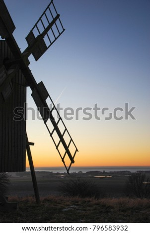 Old wooden windmill by sunset at the swedish island Oland in the Baltic Sea
