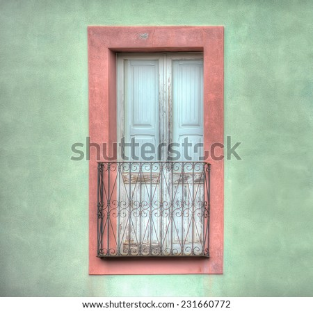 old wooden window in a green wall. Shot in Bosa, Italy. Processed for hdr tone mapping effect. - stock photo
