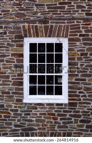 Old wooden window on a stone wall - stock photo