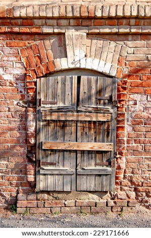 Old wooden window with its shutters closed on red brick wall.  Cracked house exterior, traditional architecture urban building in Astrakhan, Russia. Retro facade detail. - stock photo