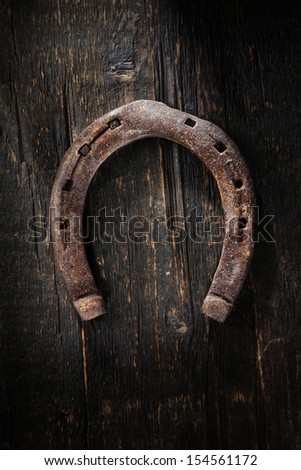 Old worn and rusty horseshoe on wooden background. - stock photo