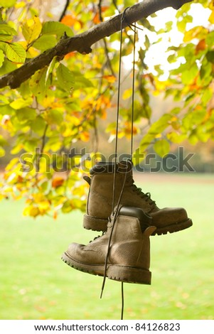 Old worn boots hanging on a tree in an autumn forest - stock photo