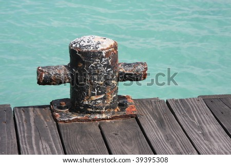 old worn down gunwale on a dock in the Caribbean with water backdrop