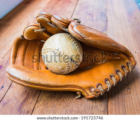 Old worn leather baseball glove and used ball on wood table - stock photo