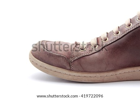 Old worn leather shoe on white background - stock photo