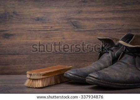 Old worn out brown leather shoes with brush over the brown background - stock photo