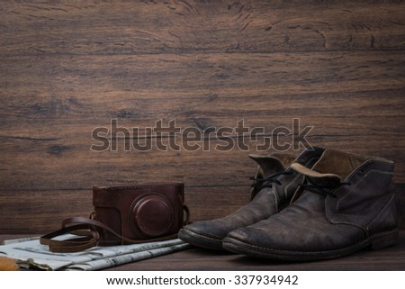 Old worn out brown leather shoes with camera and newspaper over the brown background - stock photo