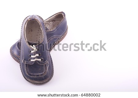 Old worn vintage baby shoes in blue, isolated on a white background