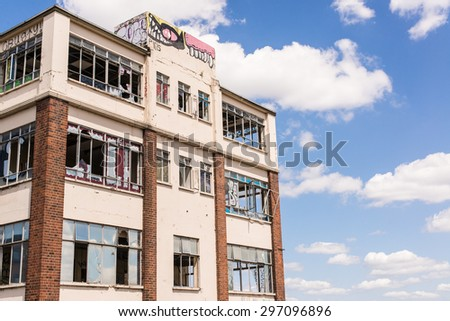 Old, wrecked and ruined industrial building with broken windows and graffiti - stock photo