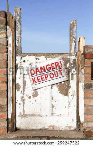 Old wrecked door with 'Danger Keep Out' warning sign - stock photo