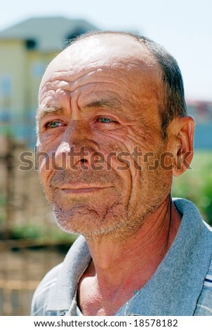 Old wrinkled man portrait with blurry background - stock photo