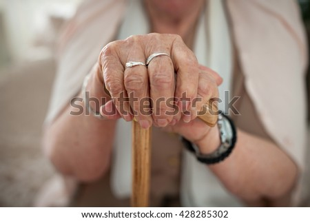 Old wrinkled woman's hands holding a walking stick - stock photo
