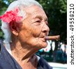 Old wrinkled woman with red flower smoking cigar. Santiago de Cuba, Cuba - stock photo