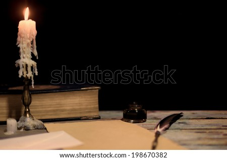 Old writing desk with its chandelier and pen - stock photo