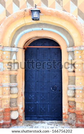 old wrought iron church door, lantern hanging over it, winter - stock photo