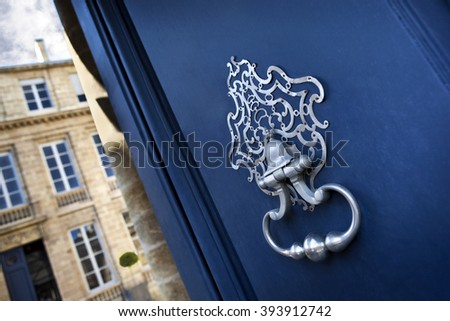 Old wrought iron knocker on a wooden door in Bordeaux, France - stock photo