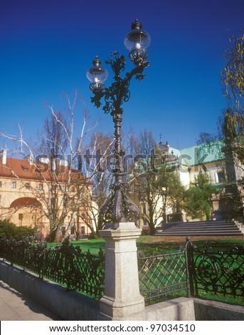 Old wrought-iron street lantern near Mickiewicz statue in Warsaw, Poland. - stock photo