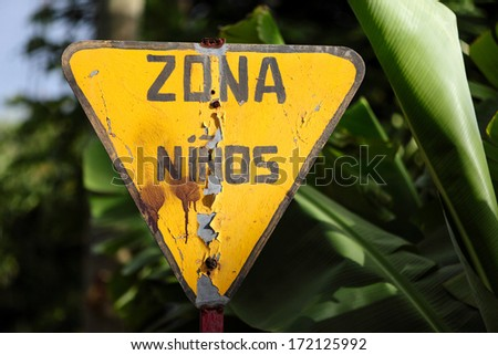 Old yellow road sign warning for children zone (=zona ninos) - stock photo