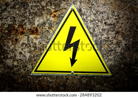 Old yellow sign with high voltage icon - stock photo