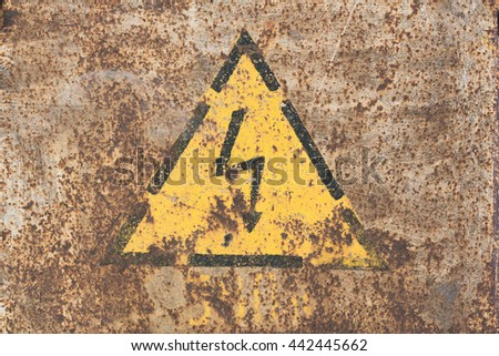 Old yellow sign with high voltage icon painted on rusty steel - stock photo