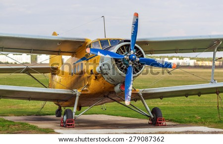 Old yellow vintage single-engined biplane with blue propeller. The plane on a background of green grass. Selective focus. - stock photo