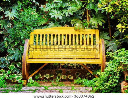 Old yellow wooden bench in garden. Vintage style. - stock photo