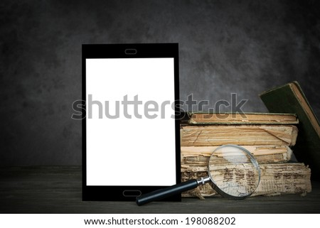 Old yellowed books,a self-designed tablet computer with blank display and a magnifier - stock photo