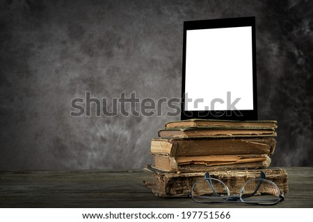 Old yellowed books, a self-designed tablet computer with blank display and reading glasses
