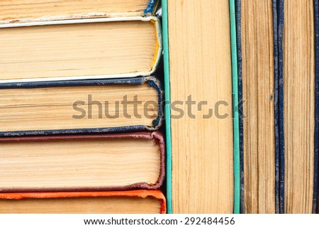 old yellowed books in a stack in the background - stock photo