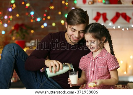 Older brother and little sister drinking milk with cookies in Christmas living room - stock photo