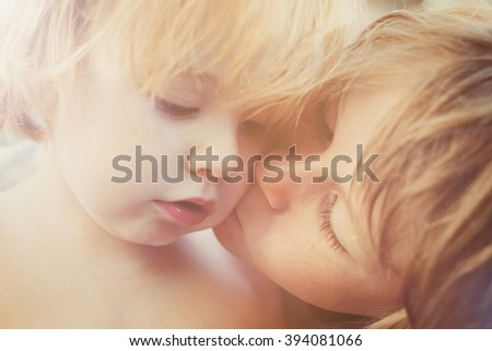 Older brother comforting his young sad brother - stock photo