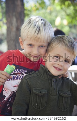 Older brother hugging his little brother in the countryside.