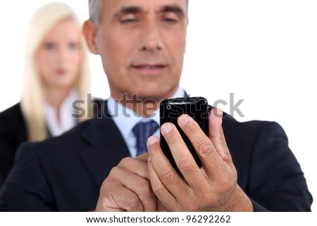 Older businessman texting on cellular phone - stock photo