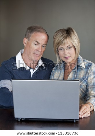 older casual couple sitting and using their laptop - stock photo