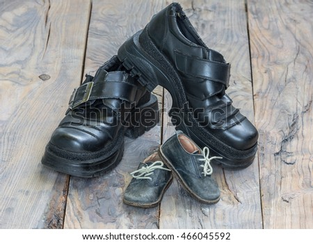 older children and adults leather shoes on the dirty wooden background