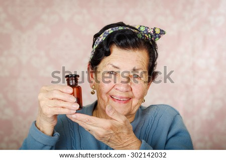 Older cool hispanic woman wearing blue sweater, flower pattern bow on head holding up a small red glass bottle and smiling to camera. - stock photo