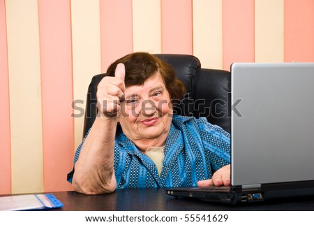 Older corporate woman giving  thumbs up and sitting at desktop - stock photo